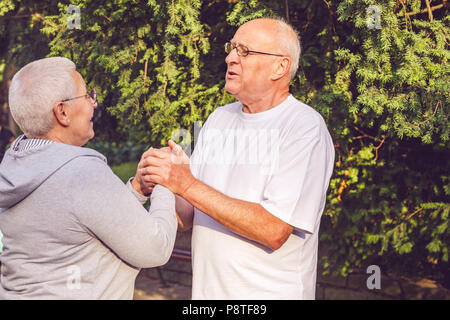 Happy family - Romantic senior couple enjoying walk in park together - Stock Photo