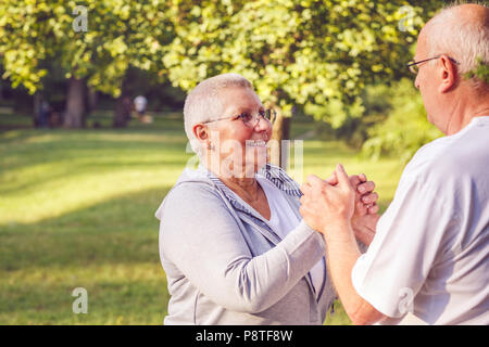 Happy family - Hands of senior couple during walk in park on sunny day close up - Stock Photo
