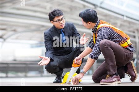 misunderstand teamwork between manager business man and young engineer discuss during project meeting at industrial construction site about the plan a - Stock Photo