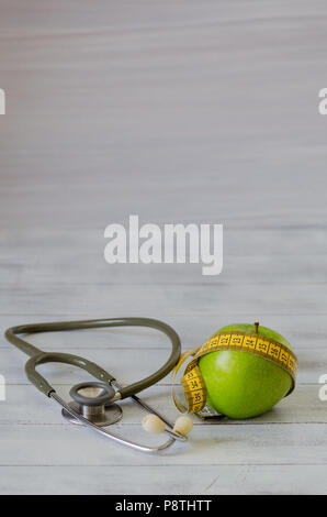 Green apple with measuring tape, stethoscope on white wooden background.Dieting concept. - Stock Photo
