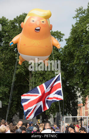London, UK. 13th July, 2018. The inflatable balloon called Baby Trump flies above Parliament Square in Westminster, the seat of the UK Parliament, during the US President's visit to the UK. Baby Trump is a 20ft high orange blimp depicting the US President as an enraged, smartphone-clutching infant - and given special permission to appear above the capital by London Mayor Sadiq Khan because of its protest rather than artistic nature. It is the brainchild of Graphic designer Matt Bonner. Credit: RichardBaker/Alamy Live News - Stock Photo