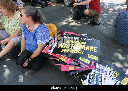 London UK. 13th July 2018.  Protesters holding placards  demonstrate  against the UK visit  of President Donald Trump as tens of thousands of protesters are expected to march to voice their displeasure against  the controversial policies of President Trump on immigration, climate change and Islamophobia. Trump dealt a double blow to U.K. Prime Minister Theresa May,criticising her plans for a soft Brexit would likely end hopes of a trade deal with the U.S. and that Boris Johnson, who quit her cabinet this week, would be a 'great' leader Credit: amer ghazzal/Alamy Live News - Stock Photo