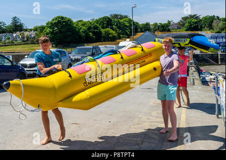 Schull, West Cork, Ireland. 13th July, 2018. Making the most of the hot weather and preparing to have some fun on towable inflatables in the water in Schull Harbour are Jamie Donnelly, Tom Casey and Jeremy Kingston, all from Cork city. The rest of the day will have highs of 20° Celsius but the rest of the weekend will be cooler with rain forecast for Sunday. Credit: Andy Gibson/Alamy Live News. - Stock Photo
