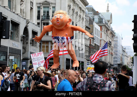 London, UK – July 13, 2018: An effigy of US president Donald Trump is help up by protesters involved in an anti-Trump march in central London, during his visit to the UK. Credit: Dominic Dudley/Alamy Live News - Stock Photo