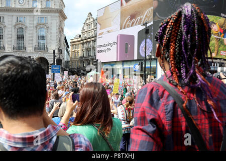 London, UK – July 13, 2018: Onlookers watch from the steps of the Eros statue in Piccadilly Circus, central London, at a demonstration to protest against US president Donald Trump Credit: Dominic Dudley/Alamy Live News - Stock Photo