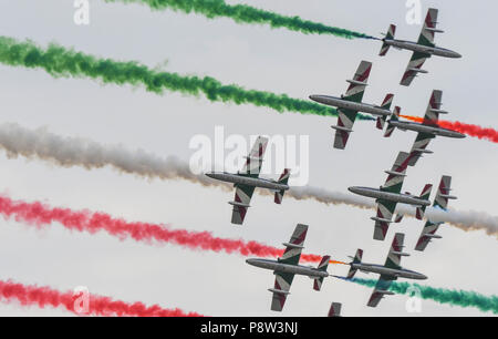 Fairford, UK, 13 July 2018. Four planes of the Italian Air Force aerobatic team, the  Frecce Tricolori, on the first day of the 2018 Royal International Air Tattoo in Fairford, England. They are flying under coloured smoke produced by other members of the team and producing their own smoke (picture taken 13 July 2018) Credit: Ceri Breeze/Alamy Live NewsCredit: Ceri Breeze/Alamy Live News  - Stock Photo