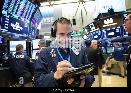 New York, USA. 13th July, 2018. A trader works at the New York Stock Exchange in New York, the United States, on July 13, 2018. U.S. stocks closed higher on Friday. The Dow Jones Industrial Average rose 94.52 points, or 0.38 percent, to 25,019.41. The S&P 500 rose 3.02 points, or 0.11 percent, to 2,801.31. The Nasdaq Composite Index rose 2.06 points, or 0.03 percent, to 7,825.98. Credit: Wang Ying/Xinhua/Alamy Live News - Stock Photo