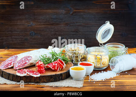 Sliced cured sausage with spices and a sprig of rosemary on dark wooden rustic background. - Stock Photo