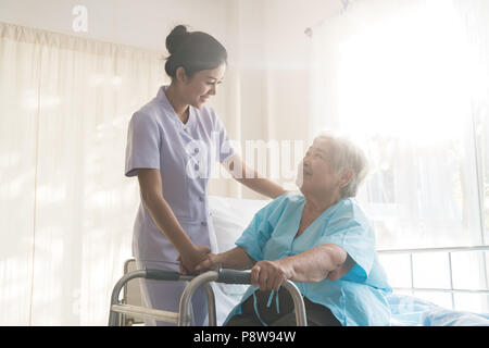 Asian young nurse supporting elderly patient disabled woman in using walker in hospital. Elderly patient care concept. - Stock Photo