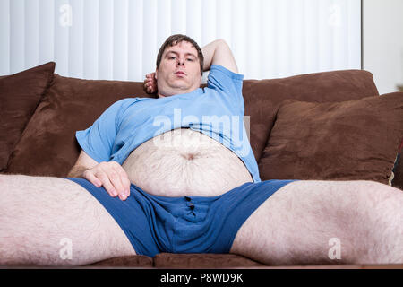 Young man sitting on couch with his legs open and his belly hanging out. - Stock Photo