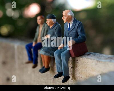 Figurines on a wooden wall.  Miniatures figurines representing of the grand parents and their grandson sitting and waiting - Stock Photo