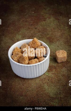 Brown sugar cubes in a ceramic bowl - Stock Photo
