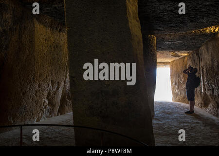Antequera, Spain - July 10th, 2018: Visitor takes pictures at interior chamber of Dolmen of Menga, Antequera, Spain - Stock Photo