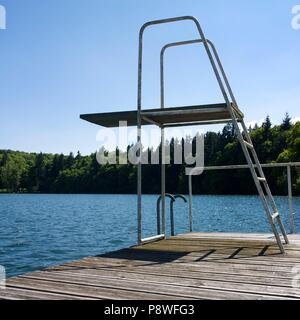 Swimming diving board and wooden pontoon at the edge of a lake surrounded the trees, Auvergne, France - Stock Photo