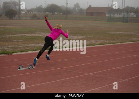 Female athlete running from starting block on the track - Stock Photo
