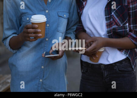 Twins siblings using mobile phone while walking on sidewalk - Stock Photo