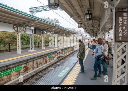 Commuters on a platform at Arashiyama statioalong the Hankyu Railway Kobe line. This is one of three major commuter rail lines in the Kobe Osaka area. - Stock Photo