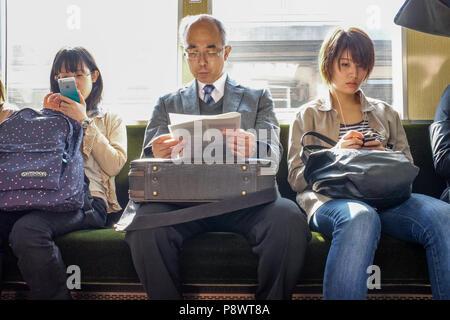 Commuters on Hankyu Railway Kobe line. This is one of three major commuter rail lines in the Kobe Osaka area. - Stock Photo