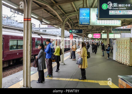 Commuters on a platform at Juso station along the Hankyu Railway Kobe line. This is one of three major commuter rail lines in the Kobe Osaka area. - Stock Photo