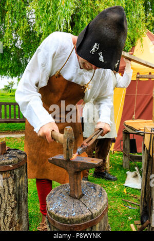 Living history, outdoor re-enactment event. Medieval mature man, blacksmith in traditional costume, using anvil while hammering red hot piece of metal - Stock Photo