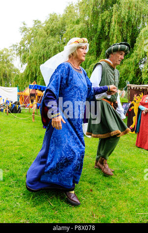 Medieval dancing outdoors. Living history couple dressed in traditional costume dancing on the grass, holding hands - Stock Photo