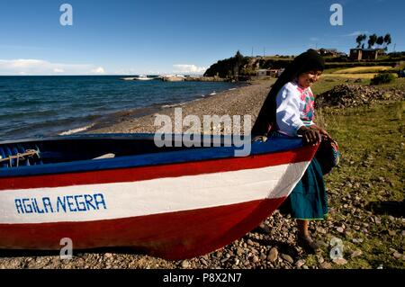 A woman from the island of Amantaní dressed in her typical regional costume next to a boat at the foot of Lake Titicaca. Amantani Island, Lake Titicaca, Puno, Peru January 2018 | usage worldwide - Stock Photo