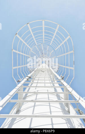 White iron staircase on the pipe rises into the blue sky without clouds - Stock Photo