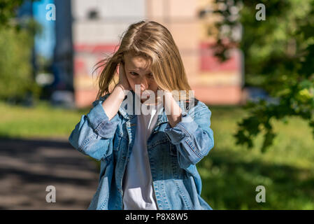 Teenage girl in summer outdoors. The palms of his hands close his ears. The concept of insult a misunderstanding, a loud noise. Emotions of discontent, bad behavior, sad and resentful child. - Stock Photo