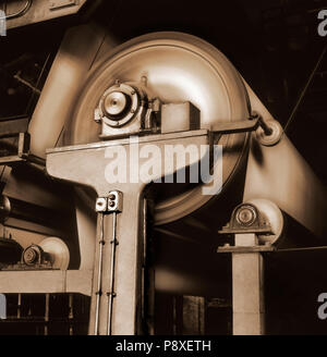 Photographic film shot. Black and white image with sepia tone and visible film grain of a papel rolling drums in an ancient factory. - Stock Photo