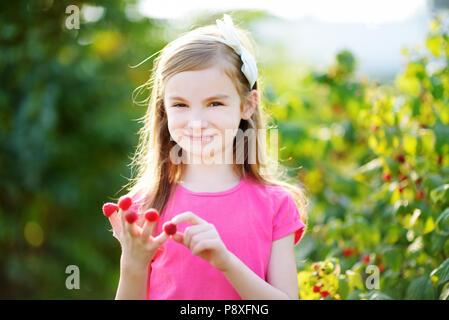 Adorable little girl eating raspberries off her fingers on bright summer day - Stock Photo