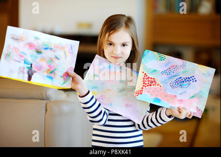 Portrait of cute little girl showing her drawings proudly - Stock Photo