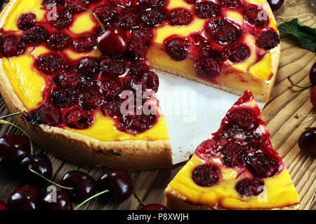 cherry cake and a bunch of cherries on table. - Stock Photo
