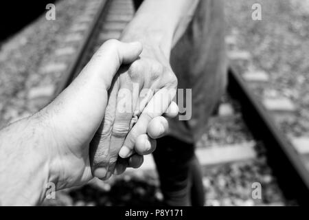 closeup of the hand of a caucasian man holding the hand of another caucasian man, seen from behind, walking by the railroad tracks, in black and white - Stock Photo