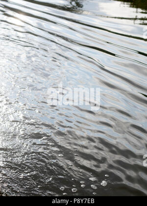 water ripples on the river reflecting the light from the sky - Stock Photo