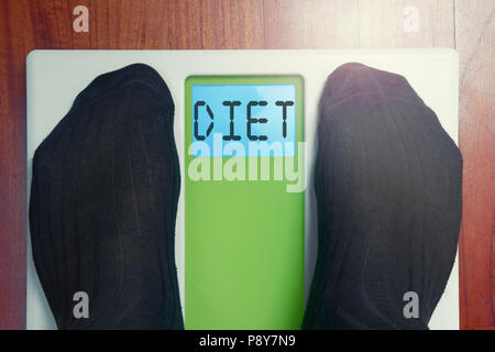Closeup male feet on scale at morning Diet word - Stock Photo