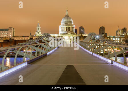 Head on landscape view of St Pauls Cathedral at night from a central position on the London Millennium Footbridge - Stock Photo