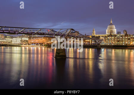 Long exposure landscape view of St Pauls Cathedral and the London Millennium Footbridge at night with lights reflected in the River Thames - Stock Photo