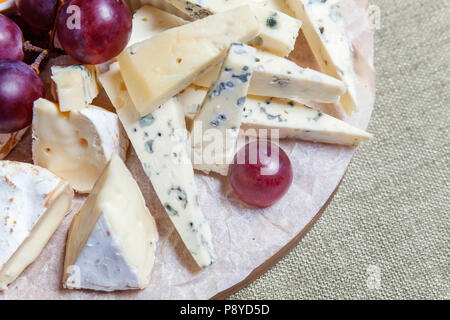 Board with different types of cheese: Dor blu, chedar, Parmesan, brie, honey sauce, finger bread and grape. Restaurant menu plate - Stock Photo