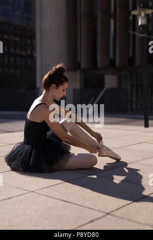 Female ballet dancer tying the ribbon on her ballet shoes - Stock Photo