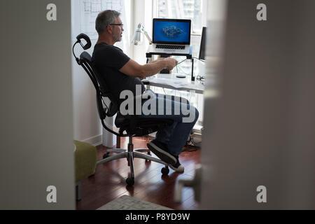 Man preparing architectural design on laptop at home - Stock Photo