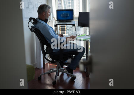 Man preparing architectural design on laptop - Stock Photo