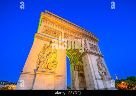 Paris, France - July 2, 2017: Night view of Arch of Triumph at the center of the Place Charles de Gaulle. Bottom view of popular landmark at blue hour with illuminated Eiffel Tower. - Stock Photo