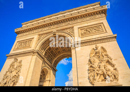 Bottom view of Arch of Triumph at center of Place Charles de Gaulle in a beautiful sunny day with blue sky. Popular landmark and famous tourist attraction in Paris capital of France in Europe. - Stock Photo