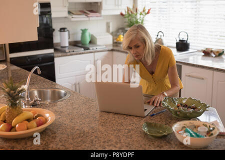 Worried senior woman checking her laptop in the kitchen - Stock Photo