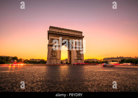 Arch of triumph at twilight. Arc de Triomphe at end of Champs Elysees in Place Charles de Gaulle with cars and trails of lights. Popular landmark and tourist attraction in Paris capital of France. - Stock Photo