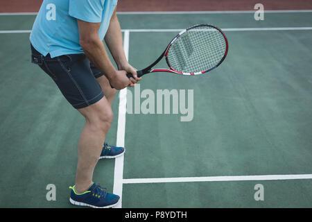 Senior man playing tennis in tennis court - Stock Photo