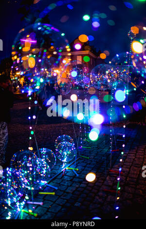 Vivid lights at night. Illuminated balloons with helium on the streets of Gniezno, Poland - Stock Photo