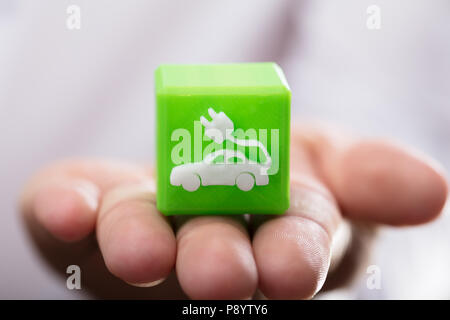 Close-up of a person's hand holding green cubic block with eco car icon - Stock Photo