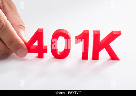 Businessperson holding red 401k pension plan on white background - Stock Photo