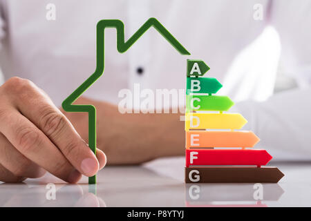 Businessperson's hand holding outline of house model with energy efficiency rate on reflective desk - Stock Photo